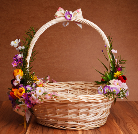 basket decorated with flowers on wooden table photo