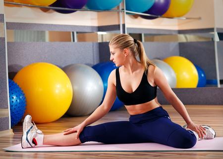 mooie blonde voert oefeningen in sporthal