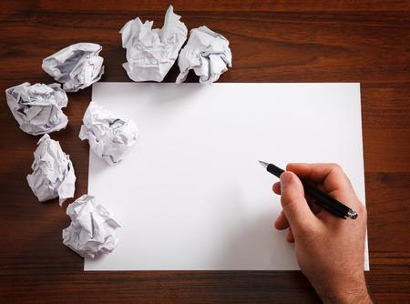 hombre escribiendo: Papel en blanco a la espera de idea con sirve la mano y la pluma