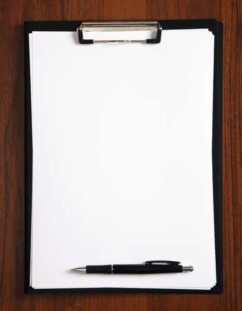 blank clipboard with a pen on   table photo