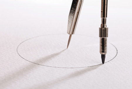compass: pair of compasses drawing circle on a paper Stock Photo