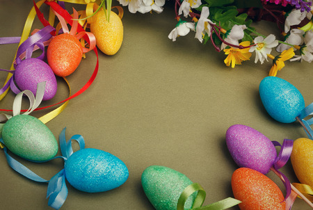 Easter flower arrangement and colorful eggs on green background with space for text photo