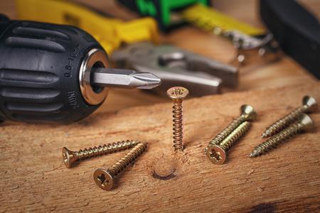 herramientas de carpinteria: Tornillo que se atornilla en un pedazo de madera  Foto de archivo