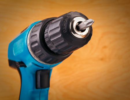 bit background: electric drill with drill bit on a wooden background