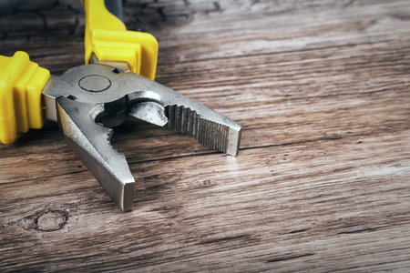 flatnose: Close up of a multitool pliers on wooden background Stock Photo