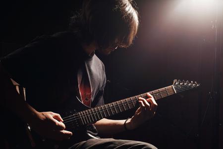 gitara: młody gitarzysta gra na gitarze elektrycznej