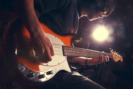concierto de rock: chico tocando el bajo, la guitarra de cerca ??