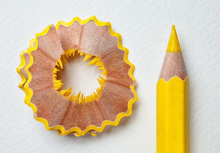 yellow pencil and shavings on white background Imagens