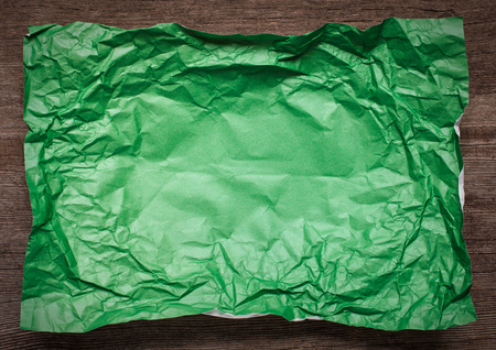 tex: Green Crumpled paper on wooden background, place for tex