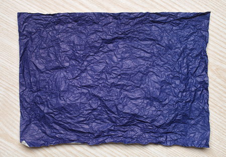 tex: Crumpled  violet paper card on wooden background, place for tex