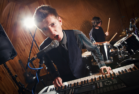 keyboard player: beautiful singer keyboard player sings into a microphone Stock Photo