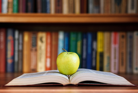 thesaurus: apple and book on background bookshelf Stock Photo