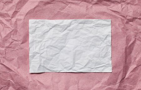 tex: Crumpled  white paper card on pink background, place for tex