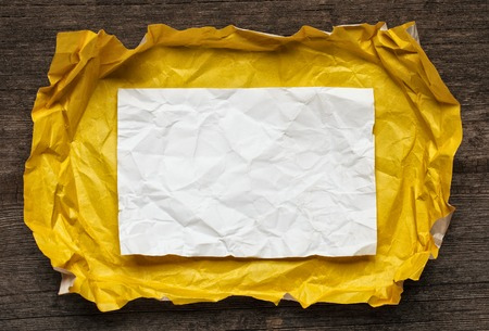 tex: Crumpled  paper card on wooden background, place for tex