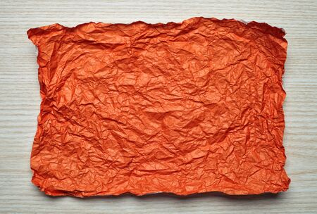 tex: Crumpled  orange paper card on wooden background, place for tex