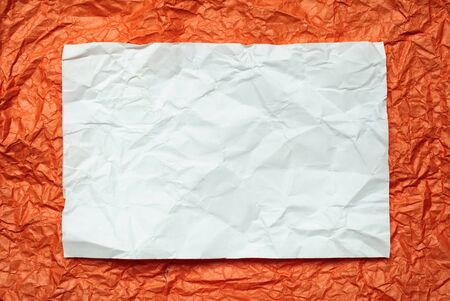 tex: Crumpled  white paper card on orange background, place for tex