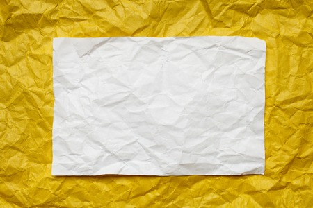 tex: Crumpled  white paper card on yellow background, place for tex