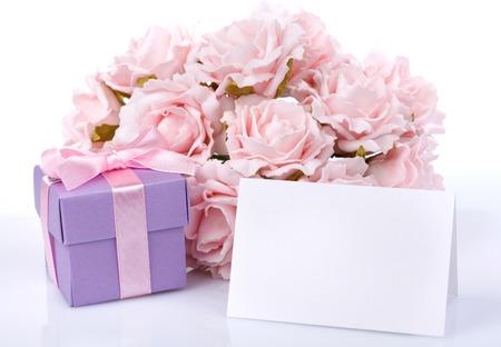 Wenskaart met roze bloemen en een paarse geschenkdoos met lint en boog op een witte achtergrond Stockfoto