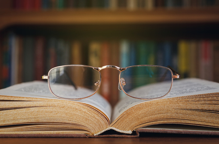 researching: glasses and book on background bookcase