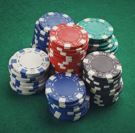 poker: chips for poker on green playing table