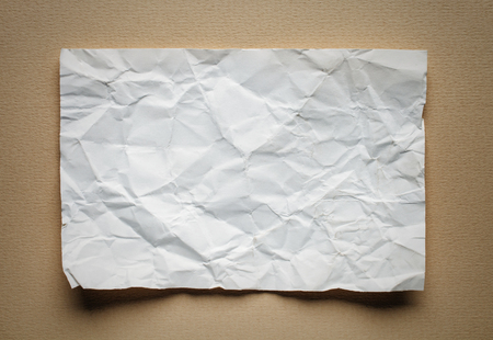 tex: Crumpled  white paper card on beige background, place for tex