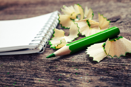 pensil: notebook with pensil and pencil shavings on wooden background Stock Photo