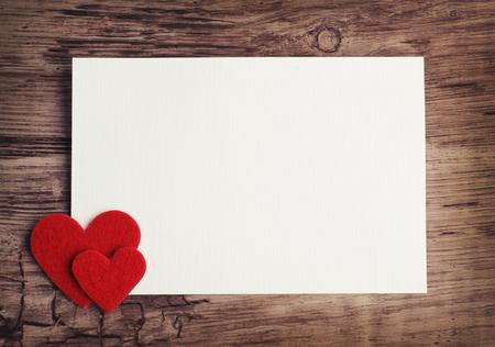 wenskaart met een rode harten en ruimte voor tekst op een houten achtergrond