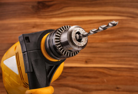 bit background: electric drill with bit on a wooden background