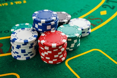 sports backgrounds: chips for poker on green playing table