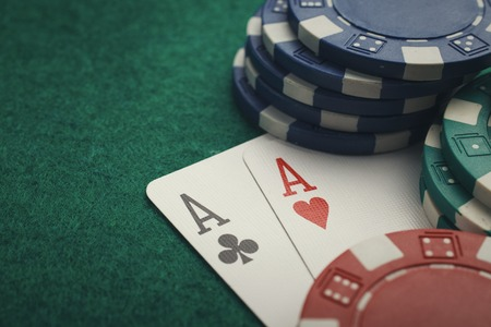 poker card: Stack of chips and two aces on the table on the green baize - poker game concept