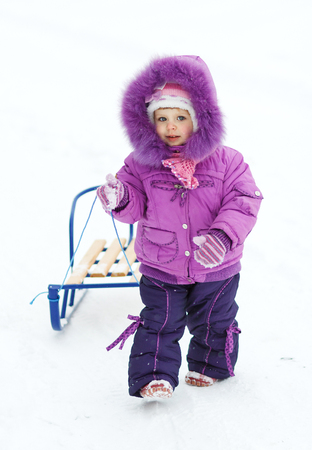 baby girl with sledges in winter clothing