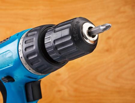 herramientas de trabajo: taladro eléctrico con broca en un fondo de madera