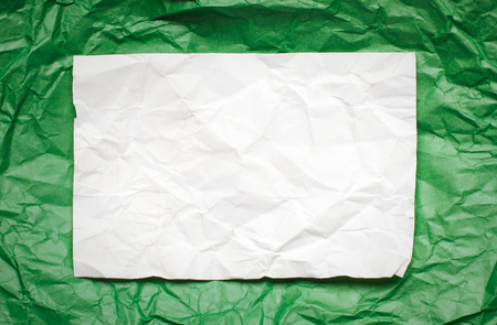 tex: Crumpled  white paper card on green background, place for tex Stock Photo