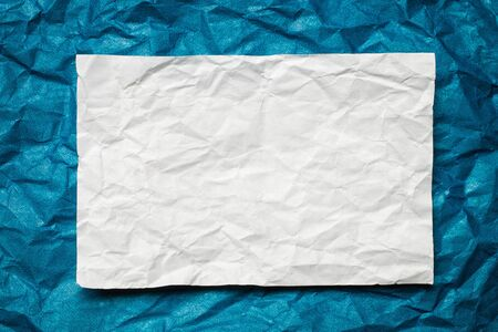 tex: Crumpled  white paper card on blue background, place for tex