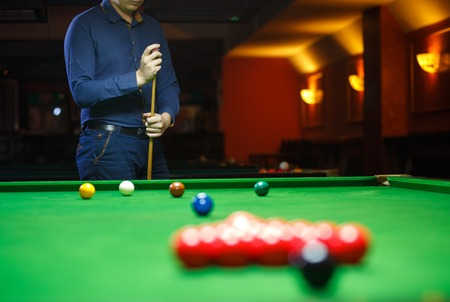 cue sticks: A young man lines up his shot as he breaks the balls for the start of a game of snooker
