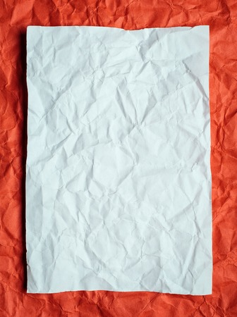 tex: Crumpled  white paper card on red background, place for tex