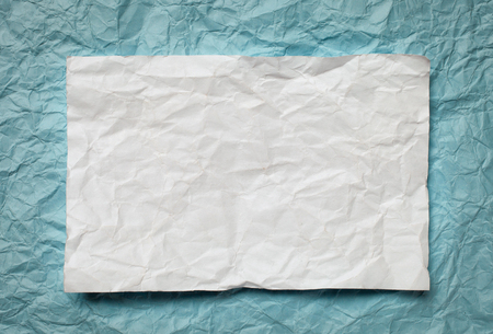 tex: Crumpled  white paper card on cyan  background, place for tex