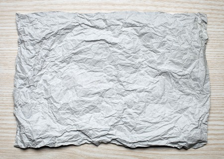 tex: Crumpled  white paper card on wooden background, place for tex