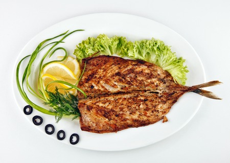 gril: roast fish with lemon, onion and olives,lemon isolated