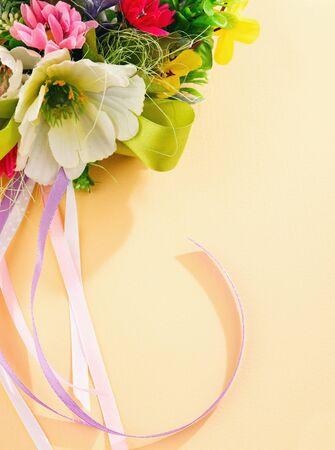 künstliche Blumen und Luftschlangen auf cremefarbenem Hintergrund mit Platz für Etiketten