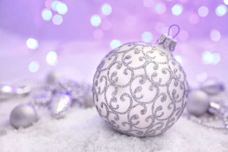 ribon: Christmas decorations silver Christmas ball with ribon in the snow on abstract background
