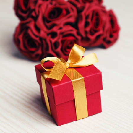 red gift box: red roses and red gift box with yellow ribbon on wooden surface
