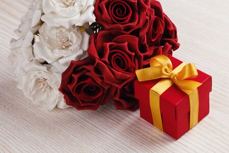 red gift box: red and white roses and red gift box with yellow ribbon on wooden surface