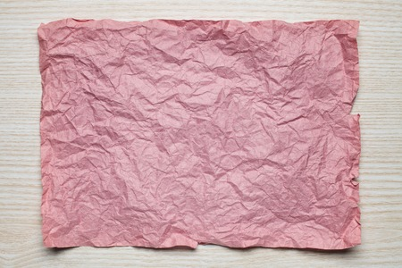 tex: Crumpled  pink paper card on wooden background, place for tex