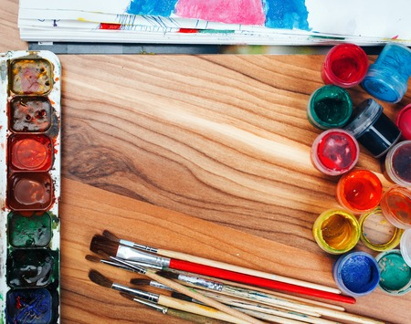 color pencil: Colorful paints and brushes arranged as a frame on wooden table