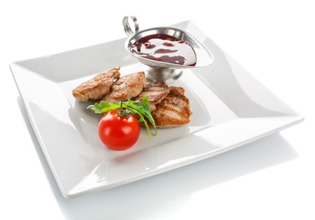 peppered: A grilled serving of succulent tender peppered steak garnished with tomato and fresh herbs and sauce on white background