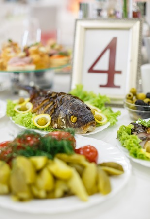 stuffed fish: Decorated catering banquet table with different food snacks and stuffed fish on corporate birthday party event or wedding celebration Stock Photo