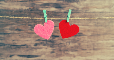 two  hearts hanging on a cord on a wooden background, love background Stock Photo