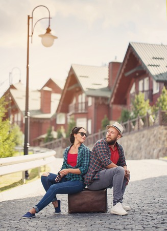 road to love: couple in love on the streets, sitting on a suitcase on the road, love. look at each other. Lifestyle.