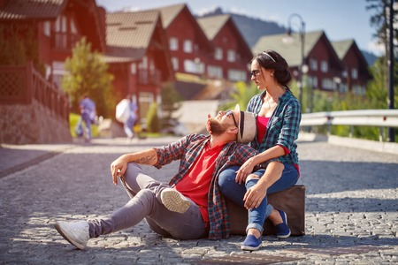 road to love: couple in love on the streets, resting on a suitcase on the road, love. Lifestyle. Stock Photo